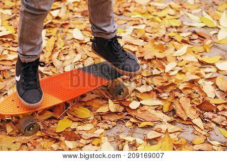 Little Boy Standing On A Orange Skateboard Outdoors. Closeup Image Of Children's Feet At Skateboard.