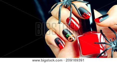 Halloween manicure design ideas. Halloween Nail art design. Nail Polish. Beauty hands. Trendy Stylish Nails and Nailpolish bottle. Black nailpolish with blood drips and pumpkin. Isolated on black