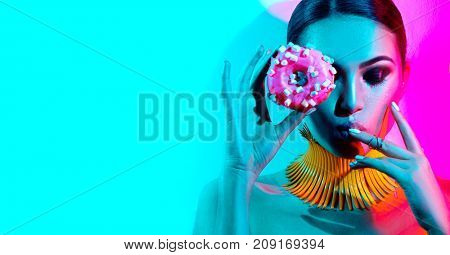 High Fashion model woman posing in studio with donut in colorful bright lights, portrait of stylish party girl with trendy make-up, haircut. Art design colorful make up. On colourful vivid background