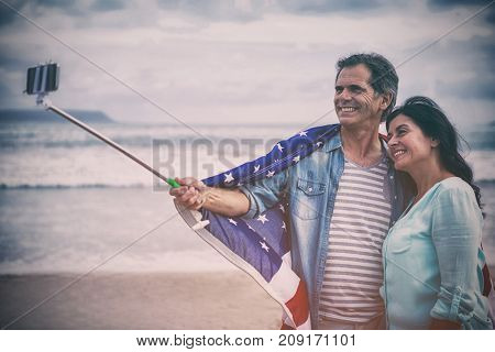 Happy couple with American flag taking selfie
