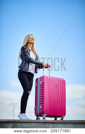 Young, beautiful blond girl with a pink suitcase on a beautiful blue sky background