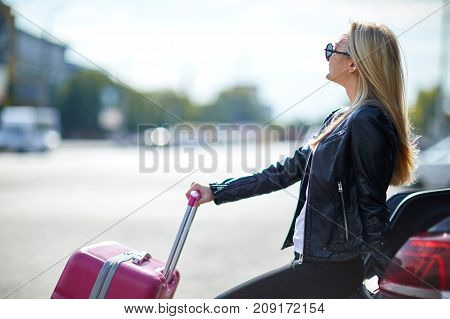 Young, beautiful girl in glasses with a pink suitcase sits on the trunk of a car against the background of a sunny sky