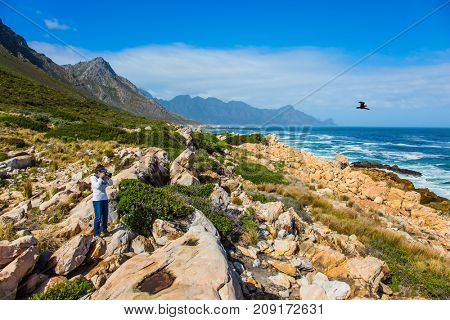 Woman taking pictures of ocean surf. Mysterious South Africa. The place where two oceans - Atlantic and Indian meet. The concept of extreme and exotic tourism