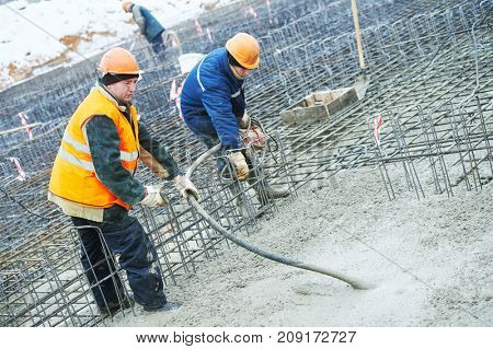 concreting work. Two concreter with vibration tool
