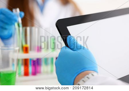 Male technician arms in protective gloves hold tablet pc pad closeup with colleague working in background with vials and sample bottles. Medical worker use reagent tube for toxic reaction process
