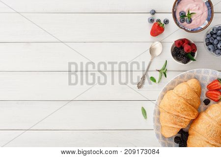 Rich continental breakfast. French crusty croissants, muesli, greek yogurt and lots of sweet berries for tasty morning meals. Delicious start of the day. Top view with copy space on white wood
