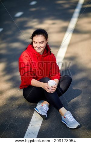 Young beautiful girl sits on the ground in a red uniform on a sunny autumn day