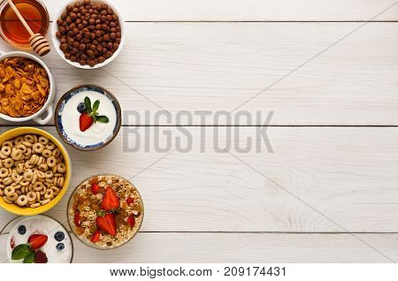 Healthy breakfast meals on wooden table copy space. Muesli, cornflakes, chocolate cereal balls and yogurt with berries frame, top view
