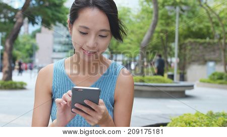 Woman using mobile phone at outdoor park