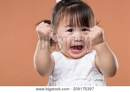 Excited baby girl holding arm fist