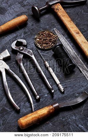 Set Of Cobbler Vintage Tools Pliers, Nippers, Hook Sewing, Cobbler's Hammer On The Dark Wooden Backg