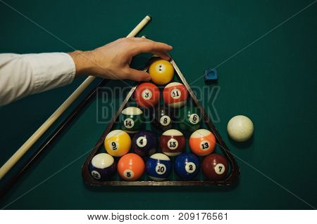 Playing billiard. Billiards balls and cue on green billiards table. Caucasian player put yellow ball inside. View from up. Billiard sport concept. Pool billiard game.