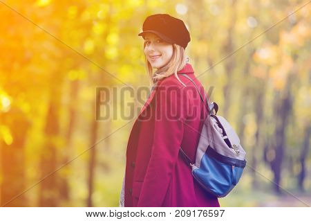 Woman In Red Coat And Backpack Have A Rest In Autum Park