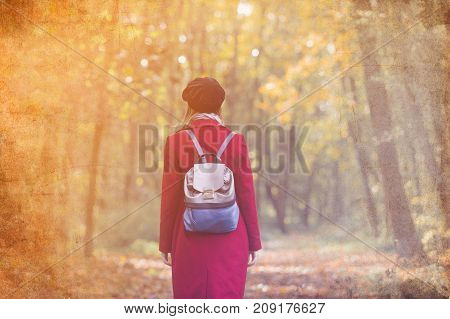Woman In Red Coat And Backpack Resting In Autum Park