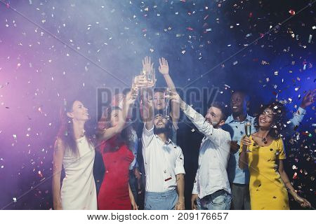 Christmas party time. Young people in snata hats toasting with champagne flutes. Multiethnic friends congratulating each other with new year. Holidays, celebration and nightlife concept