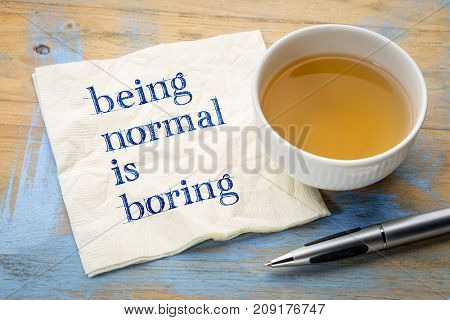 Being normal is boring  - handwriting on a napkin with a cup of tea
