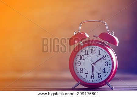 Vintage alarm clock on yellow wooden background with bokeh