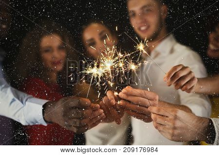 Holiday background with sparklers. Young friends holding bengal lights, closeup, selective focus. Birthday or winter holidays celebration, greeting card mockup