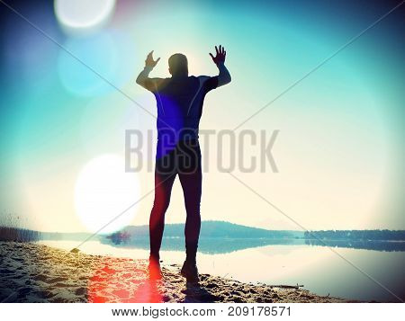 Jumping Man. Sportsman Crazy Jumping  And Jogging On Beach During The Sunrise