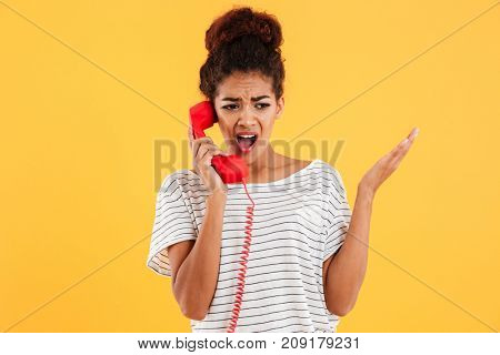 Angry african woman screaming while talking on red telephone isolated over yellow