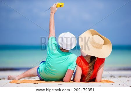 Selfie couple taking pictures on the beach. Tourists people taking travel photos on summer holidays.