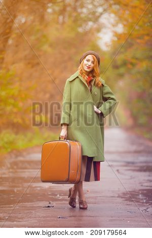 Redhead Woman In Coat With Travel Suitcase