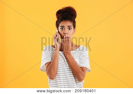 Shocked african beautiful lady talking on smartphone and looking camera isolated over yellow