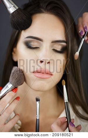 Portrait of young sexy girl with brushes for make-up. Cosmetics for face. Closeup of an attractive young female model.