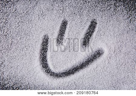 Written By A Finger Smiley Icon On The Texture Of White Sugar Crystals On A Black Background