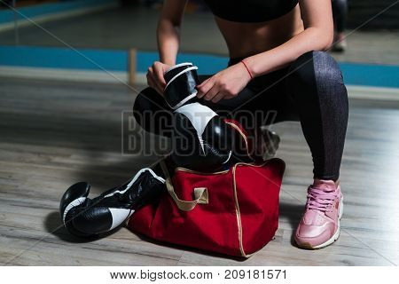 Young fighter boxer girl taking boxing gloves before  training.