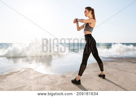 Full-length photo of young healthy woman with perfect body checking time, seaside outdoor