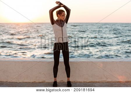 Full-length photo of young pretty woman in sport wear doing stretching exercise before  running at the seaside