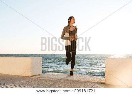 Slim woman with perfect body running at the seaside