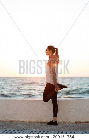 Young woman in sport wear stretching her leg muscle preparing for workout at the seaside