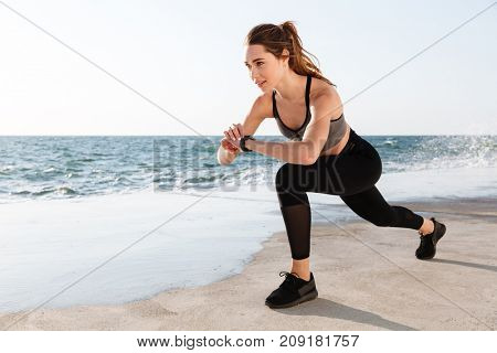 Portrait of young smiling  fitness woman checking time while doing fitness exercise for legs, seaside outdoor