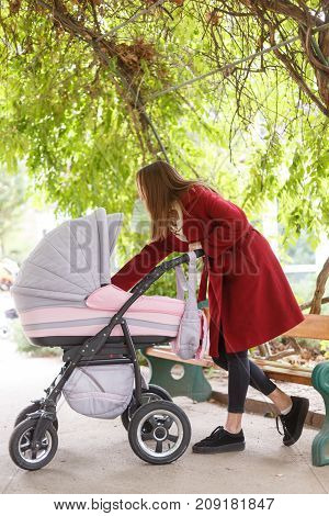 Happy young mommy spend time with a little baby in baby carriage in the park outdoors. A pretty woman take care about baby on the nature background. Full lenght of girl. Family concept.