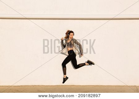Full length portrait of young healthy fitness woman in sport wear jumping near white wall