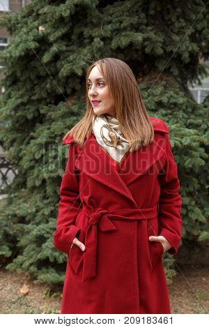 Beautiful young girl in the red coat posing on the camera in the park. Happy woman having fun on the fresh air. Full lenght of smiling girl.