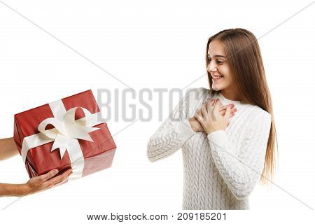 Surprise. An excited young cute girl receives a gift. It is red with a white ribbon. Girl dressed in white clothes, isolated on white background.