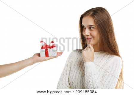 Young cute girl receives a gift. Isolated on white background. It is white with a red ribbon. The girl is dressed in white clothes.