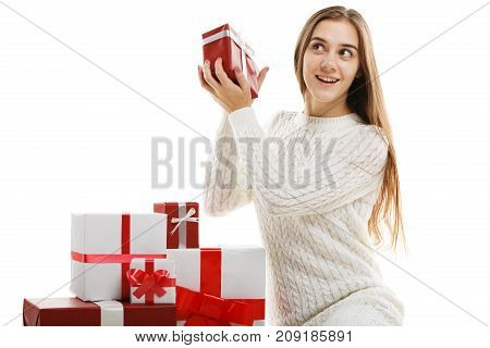 Young girl with gifts isolated on white background. Sits and unfolds a gift. The concept of a holiday. Close-up.