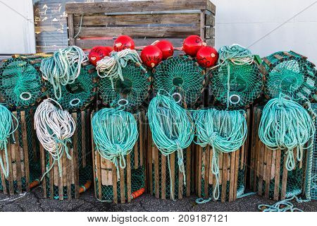 Lobster traps standing on a pier prepared for fishing with ropes and buoys in a Norwegian fishing village