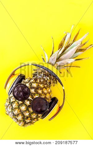 Pineapple-hipster in sunglasses and headphones on yellow background top view.