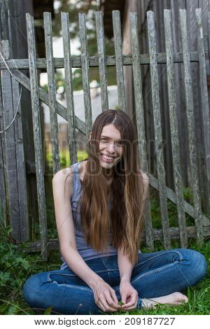 A young woman with long hair in jeans sitting on the grass near the wooden fence.