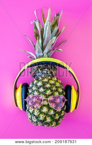 Pineapple in sunglasses and headphones on pink background top view.
