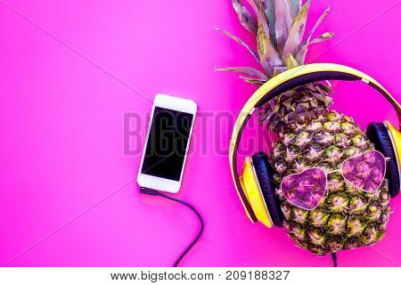 Pineapple in sunglasses and headphones is music fan. Pink background top view.