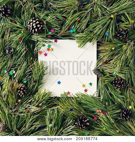 Creative background of pine branch cones and confetti star with white paper card. New Year and Merry Christmas Concept. Flat Lay