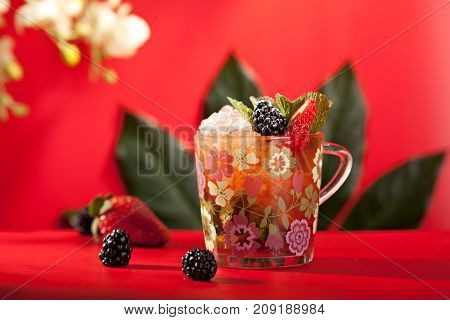 Summer Cocktail - Berry Cocktail with Soda and Ice. Cocktail decorated with Blackberry and Strawberry on Bright Red background. Leaves and Flower on Background