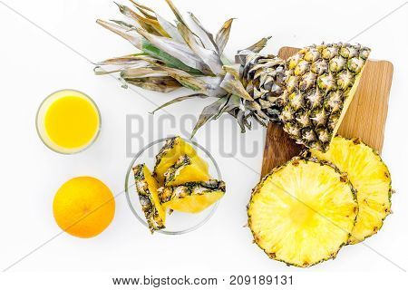 Preparing pineapple juice. Cut slices of pineapple. White background top view.