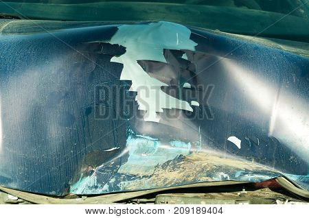 Car crash accident. Total damage on the blue car hood with broken metal parts scratched paint and rusty dirt from cooler destroyed in crash accident closeup